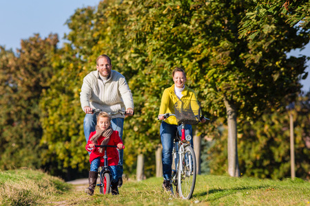 ni�os en bicicleta: Familia con la madre, el padre y la hija que viaje en familia en la bicicleta o en bicicleta en el parque