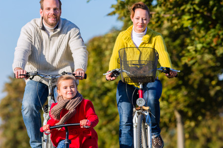 Family with mother, father and daughter having family trip on bicycle or cycle in park photo