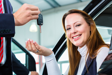 test drive: Seller or car salesman and female client or customer in car dealership presenting the interior decoration of new and used cars in the showroom and hands over the car keys