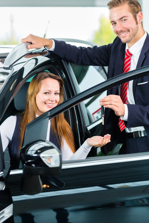 Seller or car salesman and female client or customer in car dealership presenting the interior decoration of new and used cars in the showroom and hands over the car keys photo
