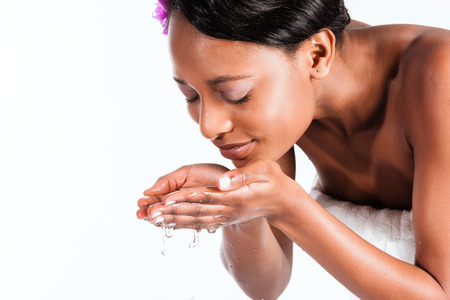 face: Young African woman in Studio doing body care with fresh water for young and beautiful skin Stock Photo