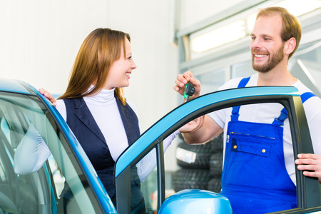 bluey: Female client and mechanic in auto workshop or MOT with car for service inspection Stock Photo