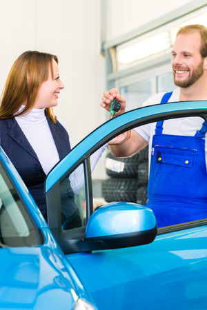 Female client and mechanic in auto workshop or MOT with car for service inspection photo