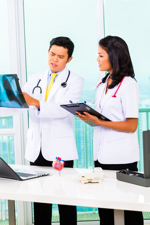Asian doctor and nurse working in medical office or practice photo