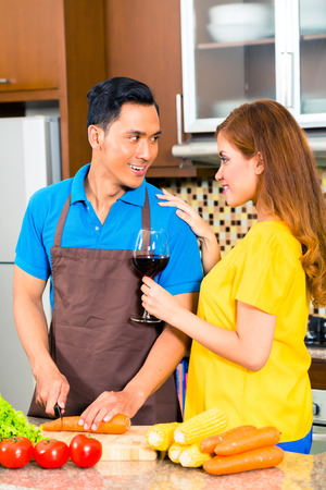 Asian couple cooking and cutting vegetables in domestic kitchen, drinking red wine photo