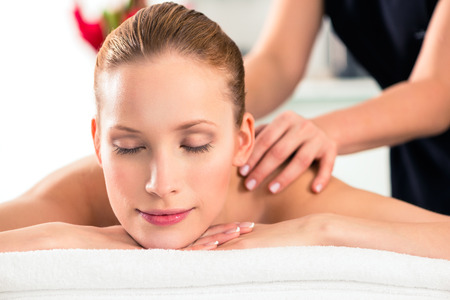 body massage: Woman in wellness beauty spa having back massage with essential oil, looking relaxed