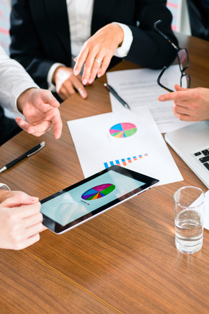 financial consultants: Business - banker, Manager or expert in meeting evaluates the figures on tablet computer and compares the development of the business to advise and act as consultant