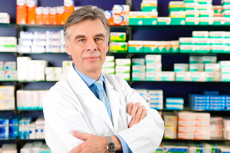 Portrait of Pharmacist in a pharmacy, he is wearing glasses and is very experienced and trustworthy