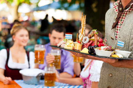 dirndl: In Beer garden in Bavaria, Germany - beer and snacks are served, focus on meal