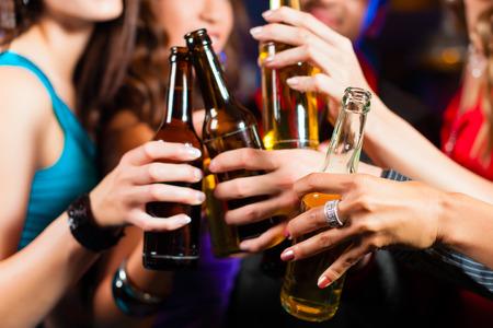 hombre tomando cerveza: Grupo de parte de personas - hombres y mujeres - bebiendo cerveza en un pub o bar