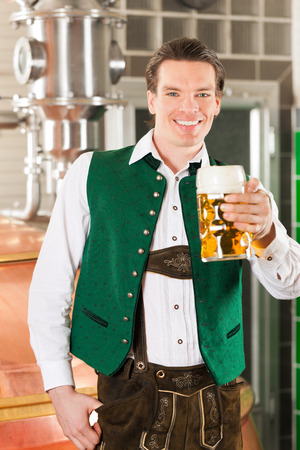 Man in Bavarian Tracht, a brewer, with beer stein in brewery photo