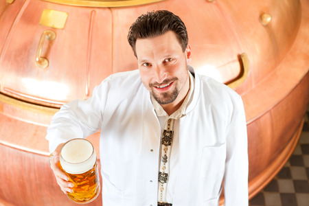 brewery: Man in Lab coat, a Brewer, with beer stein in brewery