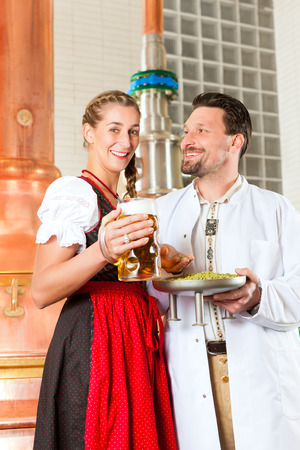 beer production: Young man and woman in traditonal Tracht with beer glass in brewery, in front of brewing kettle