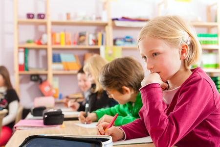 write off: Education - Pupils at primary or elementary school doing their homework or having a school test