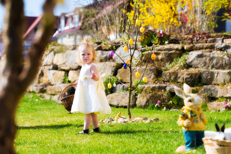 egg hunt: Little Girl on an Easter Egg hunt on a meadow in spring, she holding a basket or Easter basket Stock Photo