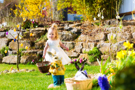 Little Girl on an Easter Egg hunt on a meadow in spring, she holding a basket or Easter basket photo