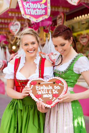 dirndl: Young women in traditional Bavarian clothes - dirndl or tracht -with a gingerbread souvenir heart on a festival or Oktoberfest Stock Photo