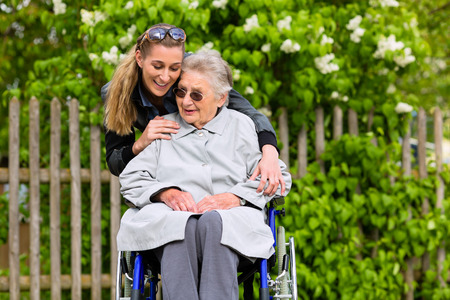 Young woman is visiting her grandmother in nursing home having a walk with here in a wheelchair photo