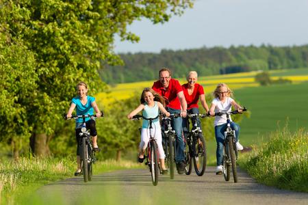 美しい風景の中自分のバイクに週末の遠足や夏の日の自転車を持つ 3 人の女の子と家族