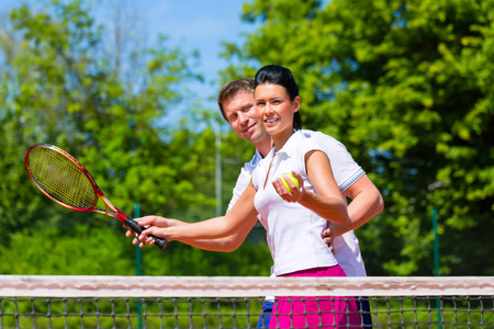 Man, tennis sport teacher, teaching woman how to play the racket sport outdoors photo