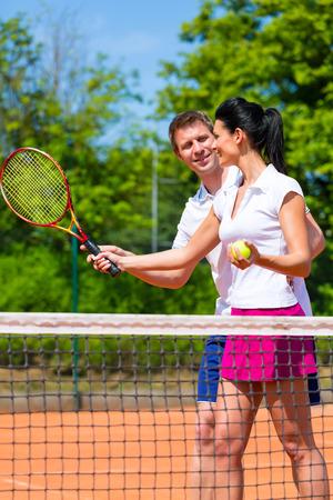 Man, tennis sport teacher, teaching woman how to play the racket sport outdoors photo
