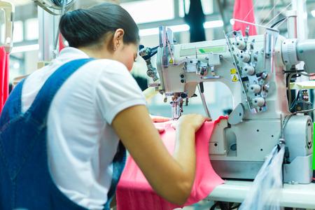 Asiatischen Näherin oder Arbeiter in einem asiatischen Textilfabrik Nähen mit einer Industrienähmaschine, sie ist sehr präzise