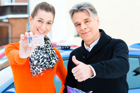 Driving school - Young woman has passed her driving test and proudly holding her driver license, the driving instructor is standing next to her Zdjęcie Seryjne