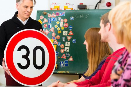 instructors: Driving school - driving instructor and student drivers with a tempo thirty Road sign, in the background are traffic signs Stock Photo