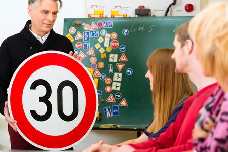 Rijschool - instructeur en student chauffeurs rijden met een tempo dertig Verkeersbord, op de achtergrond zijn verkeersborden Stockfoto