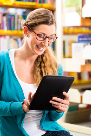 Student - young woman or girl sitting with tablet computer in a library reading an e-book photo