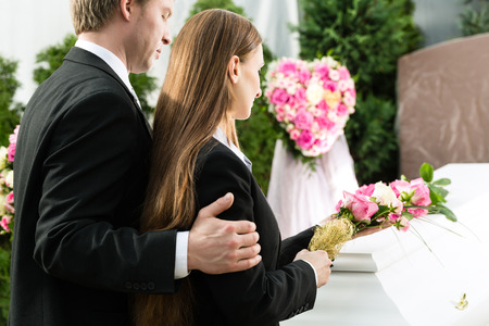 mourn: Mourning man and woman on funeral with pink rose standing at casket or coffin