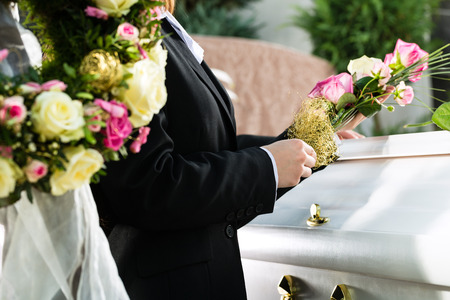 Mourning man and woman on funeral with pink rose standing at casket or coffin photo