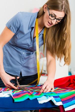 freiberufler: Freelancer - Fashion-Designer oder Schneider arbeitet an einem Design oder Entwurf und Schneidstoffe mit einer Schere