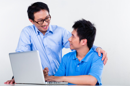 assignments: Chinese father helps his son with knowledge and experience for his complex and complicated homework assignments for the next day at school Stock Photo