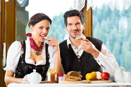 comida alemana: Pareja en un refugio de montaña tradicional con un buen desayuno