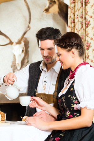 tracht: Couple in a traditional mountain hut having a meal