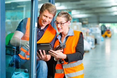 industrial worker: Logistics Teamwork - forklift driver, Worker or warehouseman and his coworker with scanner at warehouse of freight forwarding company