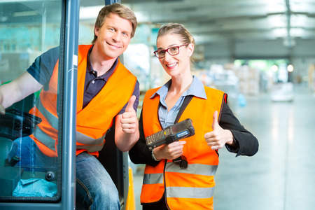 Logistics Teamwork - forklift driver, Worker or warehouseman and his coworker with scanner at warehouse of freight forwarding company photo