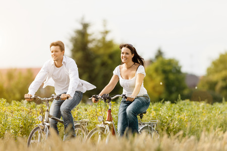 Happy young couple cycling with bicycle in summer in nature, man and woman