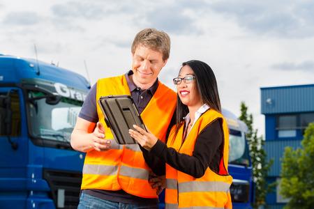 punctual: Logística - conductor orgulloso o transitario y compañera de trabajo con la computadora tablet, en frente de los camiones y remolques, en un punto de transbordo, es un equipo bueno y exitoso