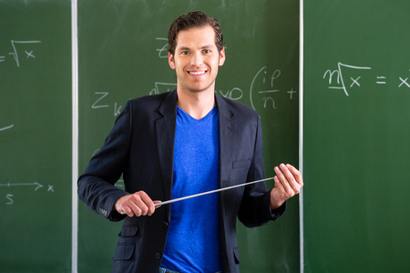 secondary: Teacher or docent in school holding a pointer in front of a blackboard in school class Stock Photo