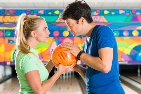 Young couple or friends, man and woman, playing bowling with a ball in front of the ten pin alley, they are a team photo