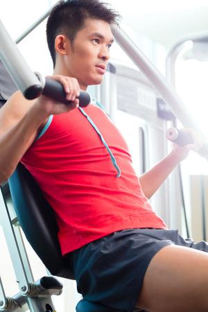 haciendo ejercicio: Hombre chino asiático que tiene el entrenamiento físico o entrenamiento en el gimnasio haciendo deporte para construir músculo en una máquina de pesas