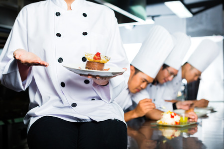 fine dining: Asian Indonesian chef along with other cooks in restaurant or hotel kitchen cooking, finishing  dish or plate for dessert
