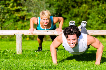 Young man and woman or personal trainer exercising pushups in City Park for sport fitness photo