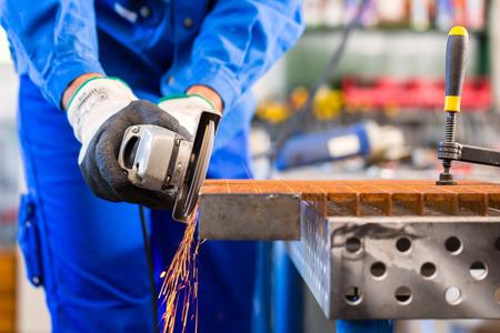 molinillo: Craftsman aserrado de metal con la amoladora de disco en el taller Foto de archivo
