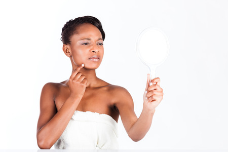 Young African woman in Studio doing body care and checking her face for pimples and spots with mirror for young and beautiful skin photo