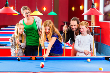 pool table: Family playing together billiard with queue and balls on pool table  Stock Photo