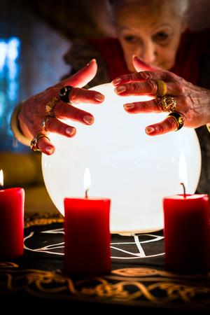 adivino: Mujer adivino o esotérica Oracle, ve en el futuro mirando en su bola de cristal durante una sesión de espiritismo para interpretarlos y para responder a las preguntas