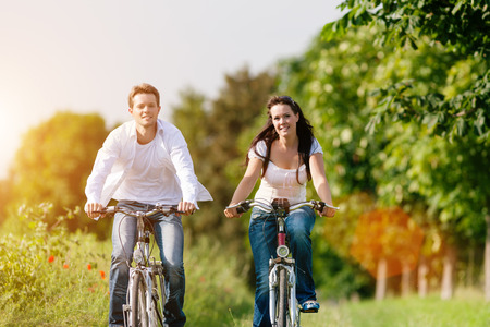 Happy young couple cycling with bicycle in summer in nature, man and woman photo